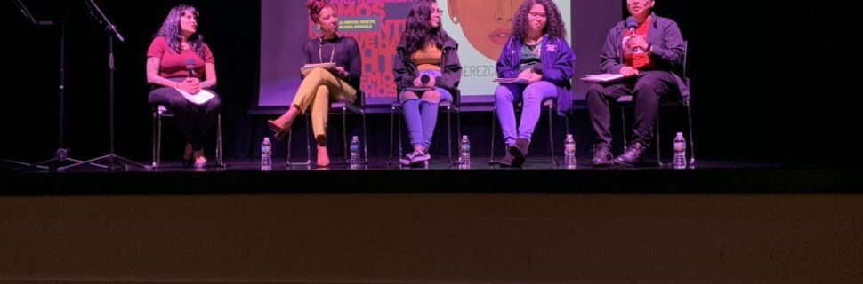 """Five Latina / Latinx people seated in front of a projected image that says """"We are Not Invisible."""""""
