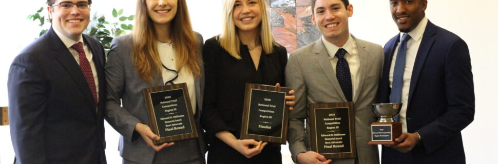 five smiling people dressed in business attire and holding three plaques and a trophy