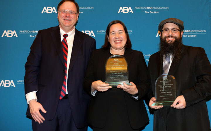 image of two men and one woman, all smiling and in business attire, with the woman and one man holding awards.