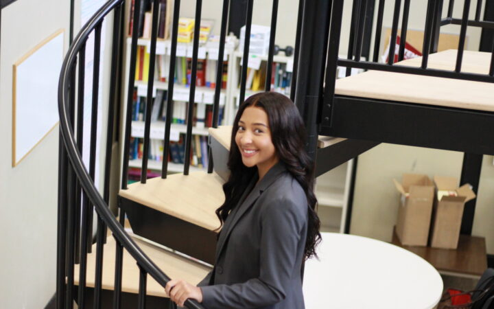 smiling African American woman dressed in business attire and ascending a spiral staircase